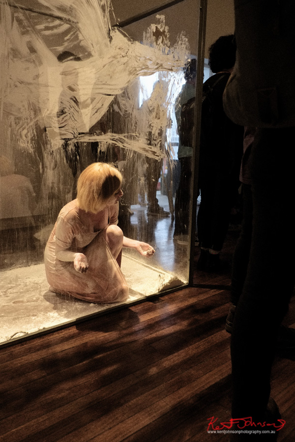Live performance piece - Woman in white smeared plastic corridor - body being dripped with Dark StickySyrup - Madeline Beckett's Press Her at KUDOS Gallery. Photography by Kent Johnson for Street Fashion Sydney.