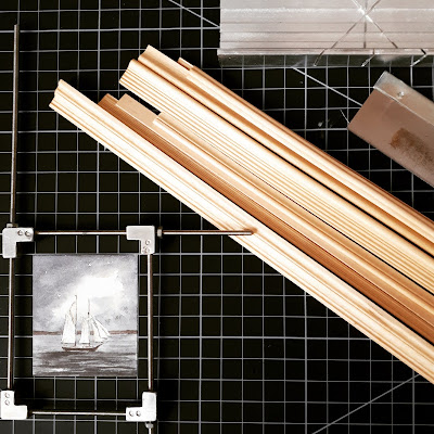 Flatlay of a cutting mat, with lengths of miniature framing, a hobby saw, mitre box and gluing jig with a picture of a boat inside it.