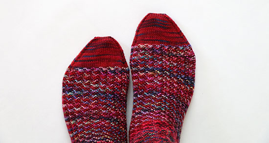 Top view of feet wearing hand knit socks in shades of red with hints of other colors, on a white background.