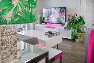 A turned on flat-screen led television in a living room with plants and attractive furniture.