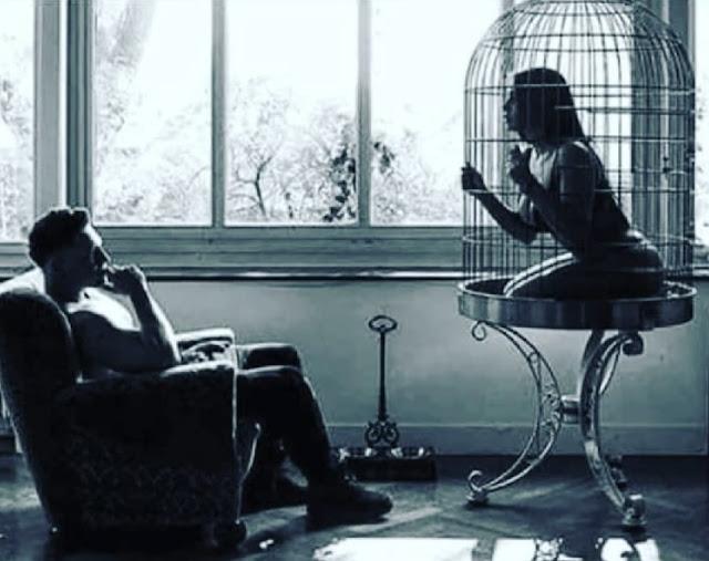 burrë ulur në kolltuk dhe grua brenda në kafaz