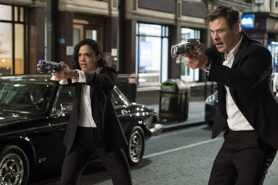 Tessa Thompson and Chris Hemsworth fight bad guys with huge space guns on an empty New York City street in a movie still for Men in Black 4
