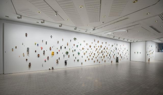 Kouvolan taidemuseo Poikilon alakerran seinä, johon taiteilija Jaakko Tornberg on ripustanut 235 kierrätysmateriaalista valmistettua robottimaista hahmoa.]