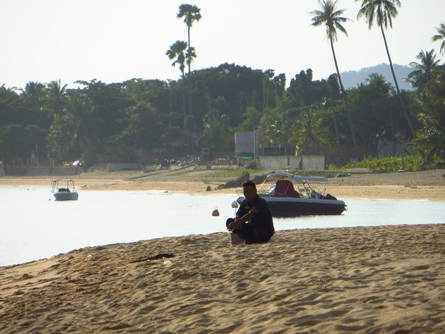 Мужчина сидит на пляже