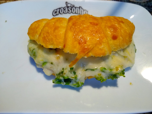 A croissant filled with broccoli and cheese.