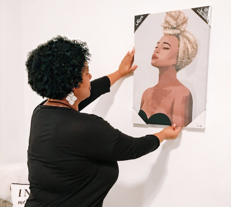 a woman hanging up an African american woman wall art