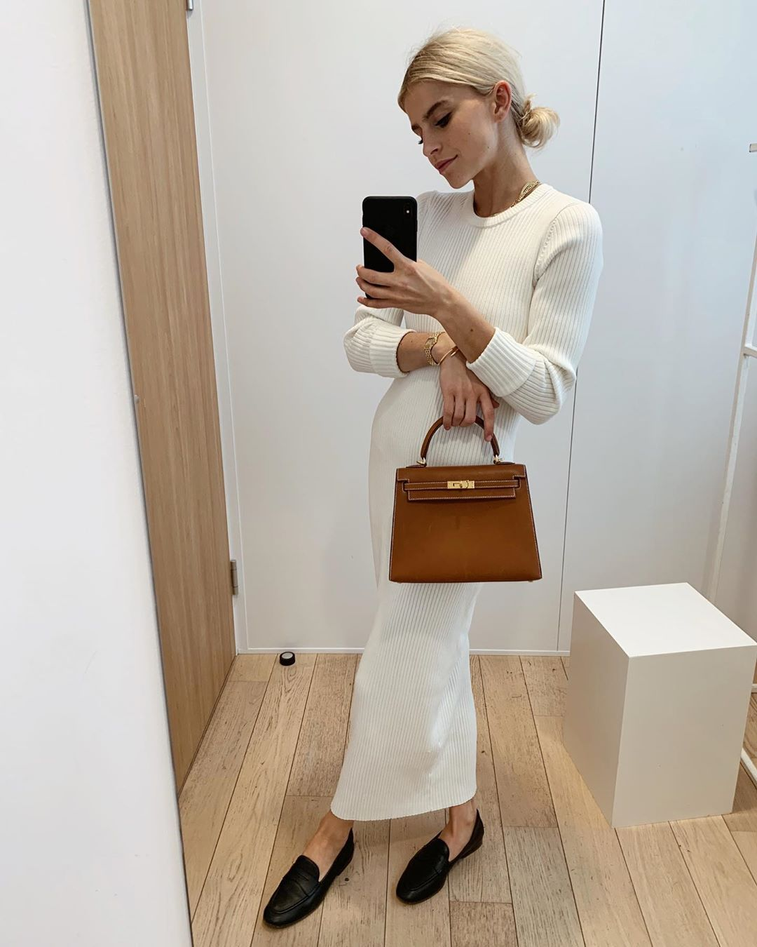 25 Top Handle Bags Cool Girls Swear By — Caroline Daur with a camel Hermes bag, white sweater dress, and black loafers