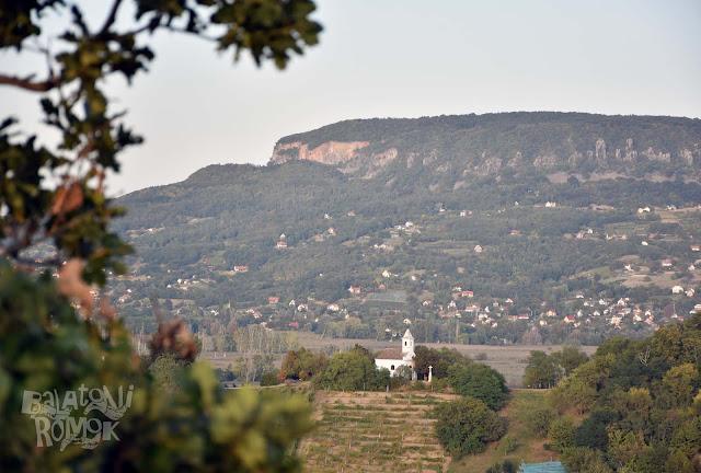 Előtérben a fehér falú, Szigligeten álló Szentháromság kápolna, háttérben pedig a Badacsony.