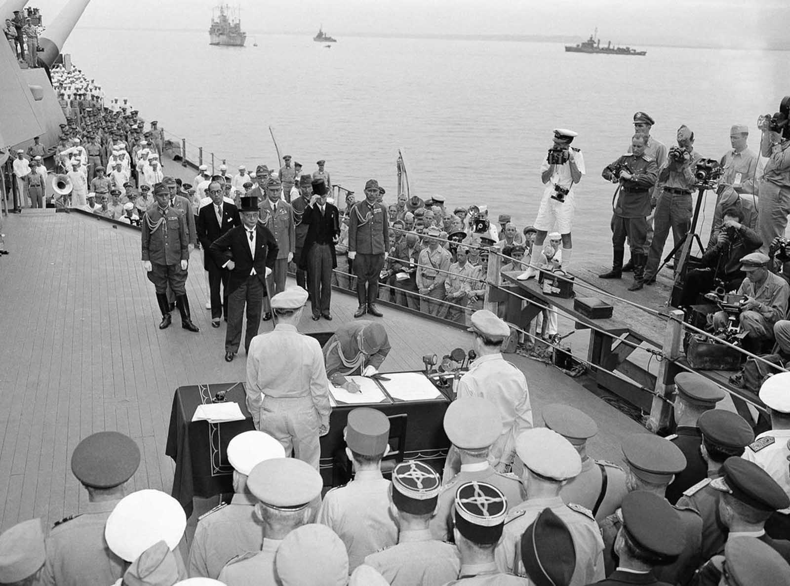 The scene aboard the battleship Missouri as the Japanese surrender documents were signed in Tokyo Bay, on September 2, 1945. Here, General Yoshijiro Umezu signs the Instrument of Surrender on behalf of the Armed Forces of Japan, Foreign Minister Mamoru Shigemitsu (behind him, in top hat) had earlier signed on behalf of the government. Both men were later tried and convicted of war crimes. Umezu died while in prison, Shigemitsu was paroled in 1950, and served in the Japanese government until his death in 1957.