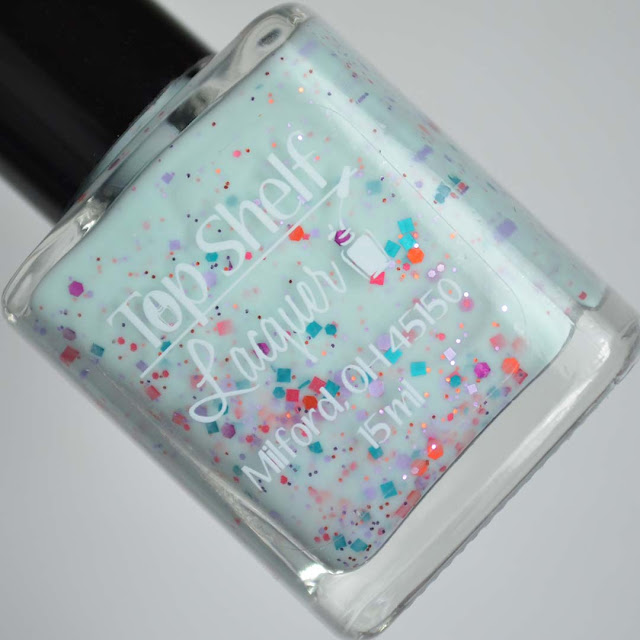teal crelly nail polish with glitter in a bottle