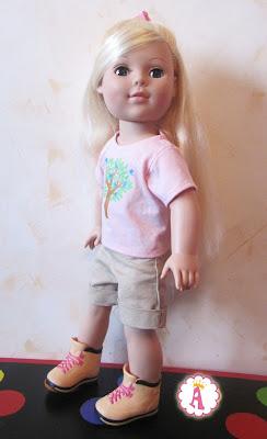 Игрушка кукла Мадам Александер стоит в кроссовках на столе