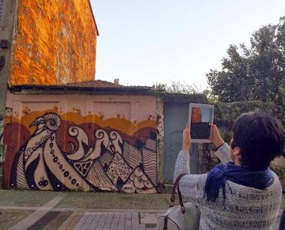 Mulher fotografando com um telefone uma parede de grafite