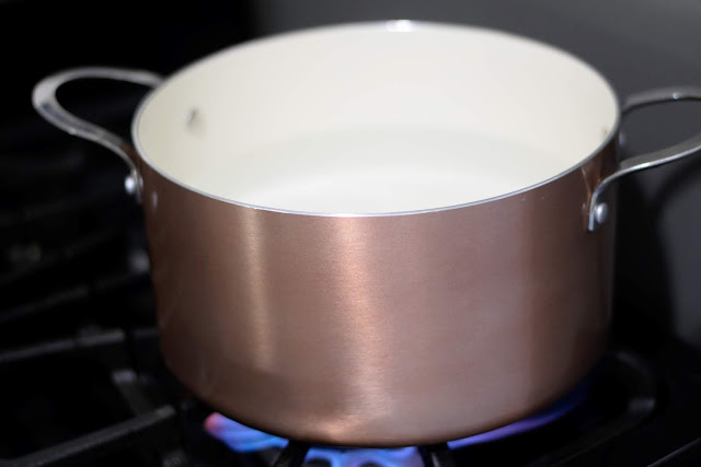 A copper pot full of water, coming to a boil on the stove.