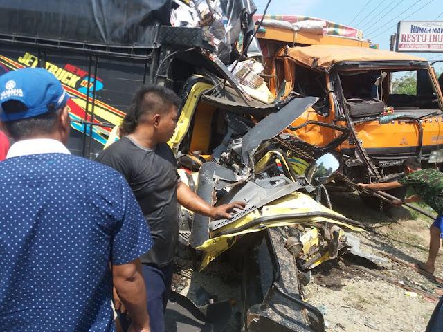 Warga menyaksikan truk dan tronton yang ringsek akibat tabrakan di Batubara.