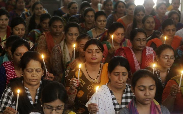 Indian staff at a school pray for the victims of Sunday's blasts in Sri Lanka, in Ahmadabad, India.