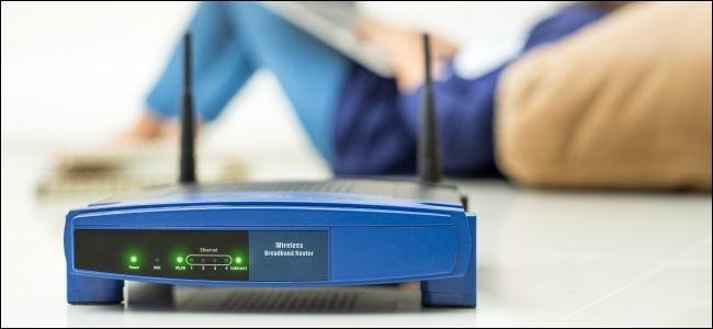 موجه لاسلكي والأطفال يستخدمون جهاز كمبيوتر محمول في المنزل
