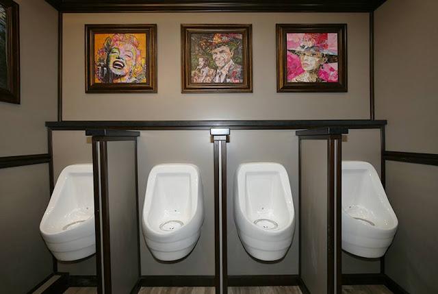 Four Sloan porcelain urinals on the Men's side