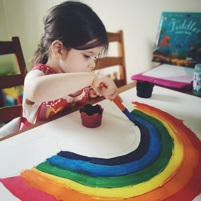 A picture of a toddler painting a rainbow