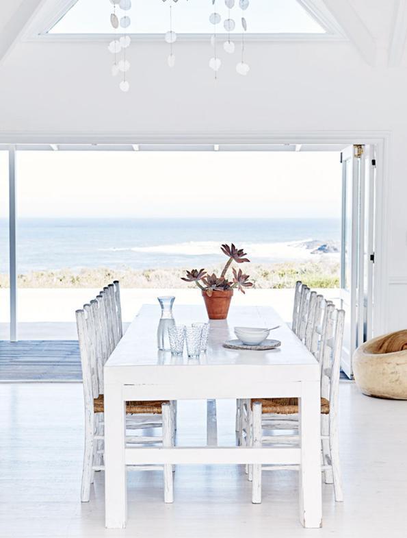 comedor con mesa de madera y sillas decapadas en blanco frente al mar chicanddeco