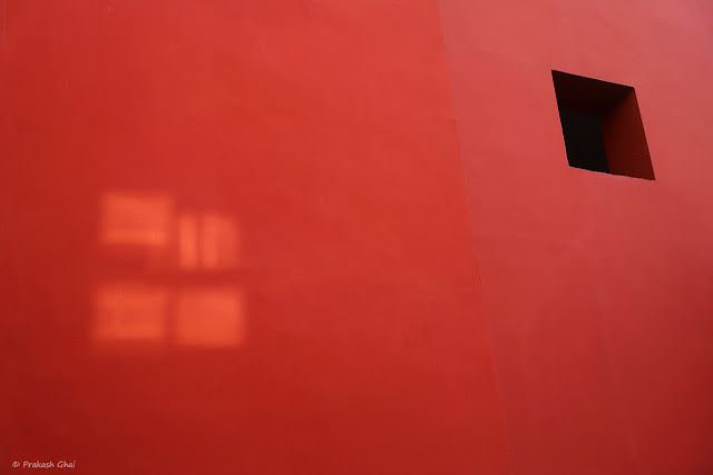 A Minimalist Photograph of a Square Versus Abstract Light Squares on a Red Wall at Jawahar Kala Kendra, Jaipur.