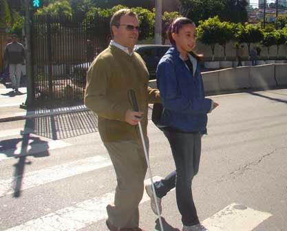 Fotografia de uma garota ajudando um cego a atravessar a rua. Ele está segurando no braço dela.