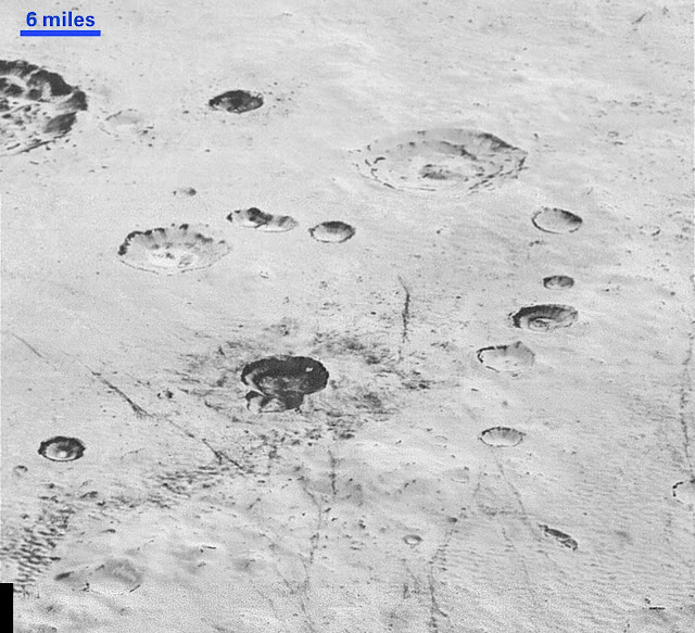 "This highest-resolution image from NASA's New Horizons spacecraft reveals new details of Pluto's rugged, icy cratered plains. Notice the layering in the interior walls of many craters (the large crater at upper right is a good example) – layers in geology usually mean an important change in composition or event but at the moment New Horizons team members do not know if they are seeing local, regional or global layering. The darker crater in the lower center is apparently younger than the others, because dark material ejected from within – its ""ejecta blanket"" – have not been erased and can still be made out. The origin of the many dark linear features trending roughly vertically in the bottom half of the image is under debate, but may be tectonic. Most of the craters seen here lie within the 155-mile (250-kilometer)-wide Burney Basin, whose outer rim or ring forms the line of hills or low mountains at bottom. The basin is informally named after Venetia Burney, the English schoolgirl who first proposed the name ""Pluto"" for the newly discovered planet in 1930. Credit: NASA/Johns Hopkins University Applied Physics Laboratory/Southwest Research Institute"