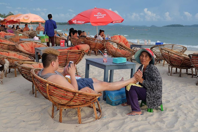 A Chinese tourist enjoys a foot massage on the beach at Sihanoukville.