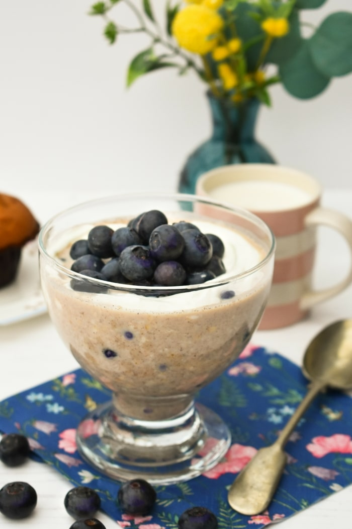 Blueberry Muffin Overnight Oats in a glass topped with yoghurt and more blueberries