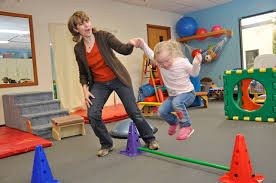 Child learning to jump hurdles in Physical Therapy Session