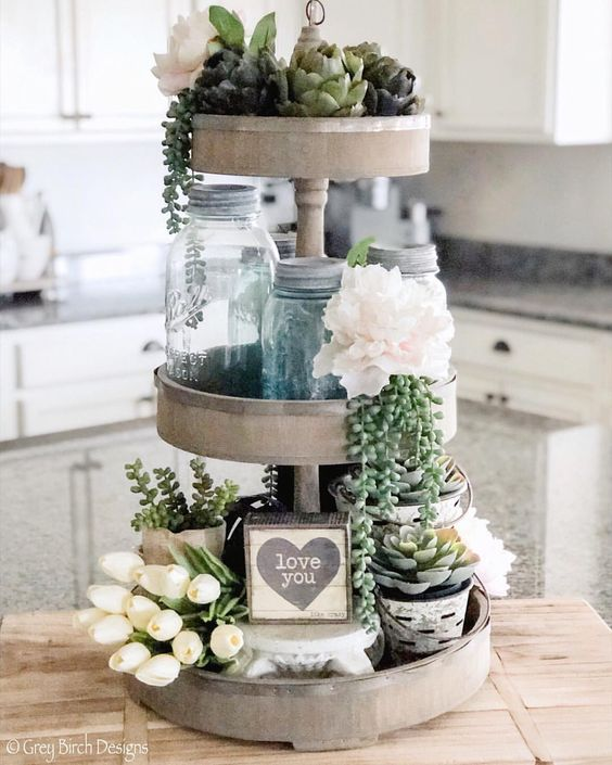 Three-tier tray with artichokes glass jars and floral decor