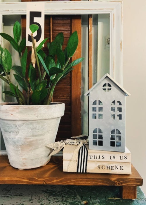 How to make a DIY decorative book stack |  add a metal house to a distressed book stack to a vintage home decor vignette