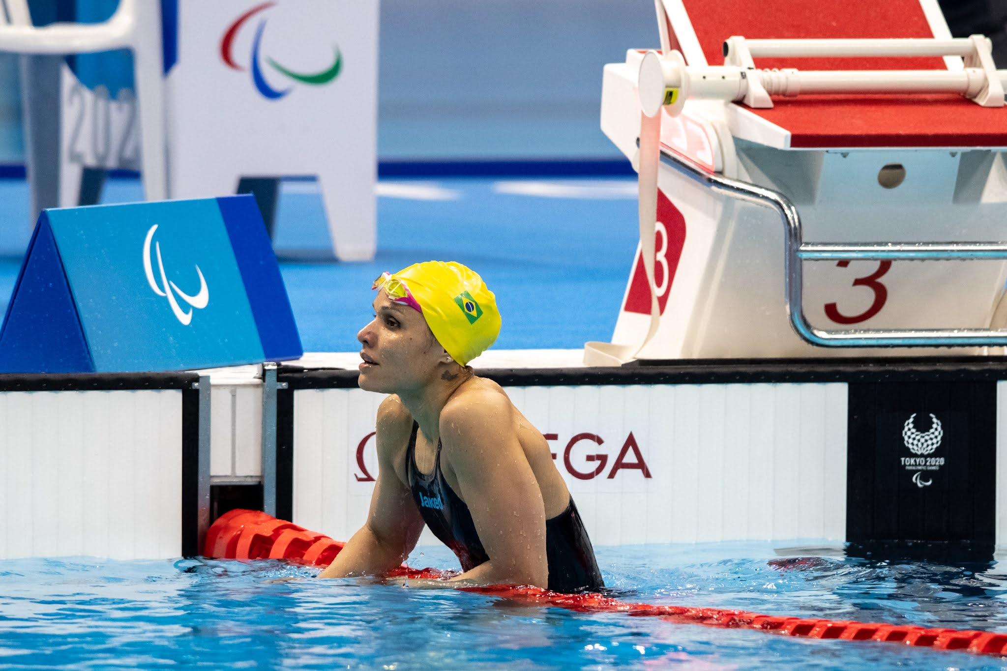 Maria Carolina Santiago, de touca amarela, está na piscina, com a mão sobre a raia
