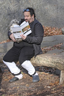 "A bearded man in his forties or fifties (can't tell) is sitting on a bench (made of stone) in Central Park. He is holding a small to medium sized white dog in his right arm and in his left hand he is holding volume one of my book series (""Words In Our Beak"") in such a manner that it appears he is reading to his dog. Information re this book as well as info re volumes two and three is on my blog @ https://www.thelastleafgardener.com/2018/10/one-sheet-book-series-info.html"