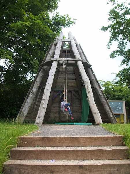 a child enjoys adventurous play on the robust wooden climbing equipment at windmill hill city farm