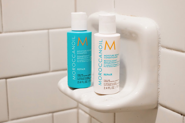 morocconoil moisutre repair shampoo and conditioner in a white tile bathroom