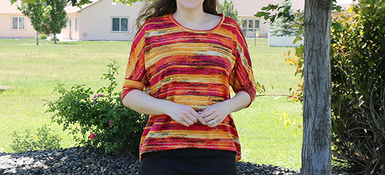 Woman wearing shirt sewn from Simplicity pattern S0340 with red, orange and black striped stretch knit fabric.