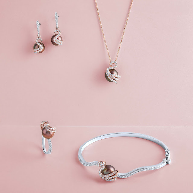 Pearl jewelry shot against a pastel pink backdrop.