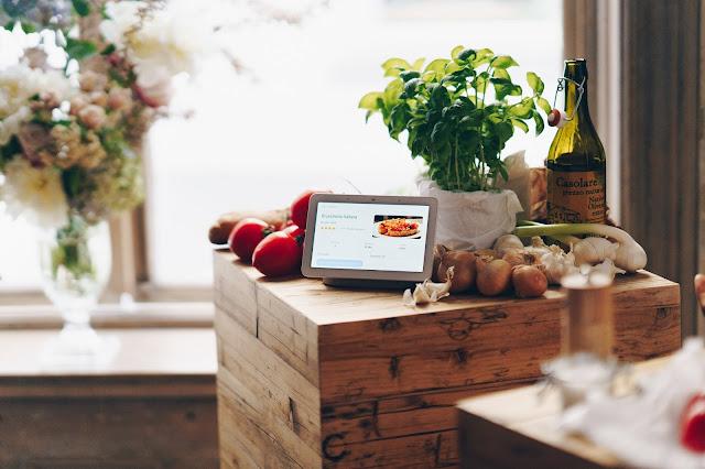 Ein Nest Hub auf einem Tisch, drum herum liegt Gemüse