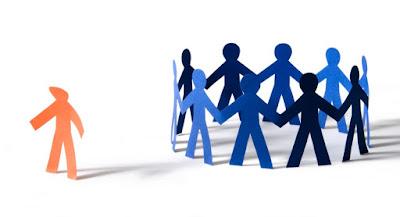 Descrição da imagem #PraCegoVer: Um círculo de figuras humanas de cartolina dando as mãos e formando um grupo, enquanto no lado esquerdo uma figura humana parecida de cor diferente aparece isolada, como se tivesse sido discriminada pelo círculo, e cabisbaixa. Fim da descrição.