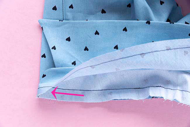 Arrow showing direction to sew stand when attaching it to bodice - sew in towards the corner
