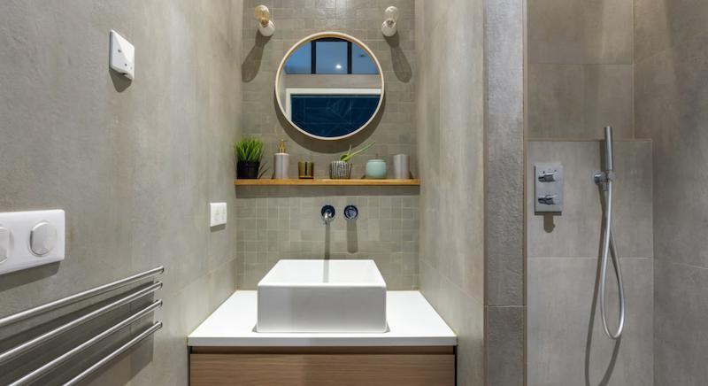 Baño con revestimiento cerámico gris.