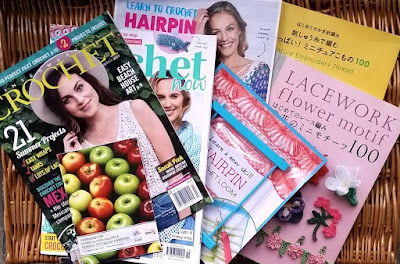 Magazines and books fanned across a brown wicker surface: (Left to right): Interweave Crochet Summer 2017, instruction booklet for Royal Adelaide Show exhibitors (apples on the cover),Crochet Now Issue 15 plus Hairpin Lace supplement and loom, Japanese crochet pattern books for miniature embroidery thread and lacework flower motifs.