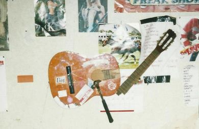 smashed up guitar on wall