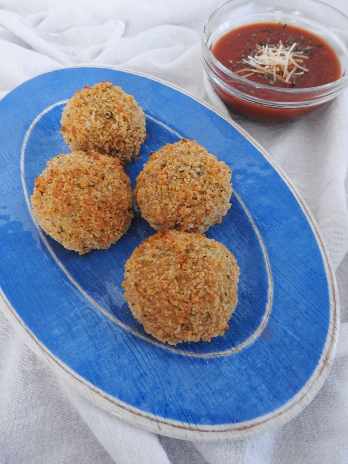 arancini on blue plate with side of sauce