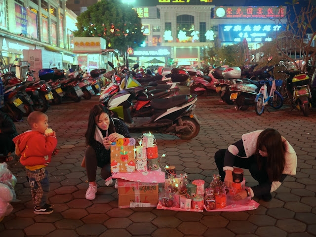 young woman setting up a display of Christmas apples in Zhongshan