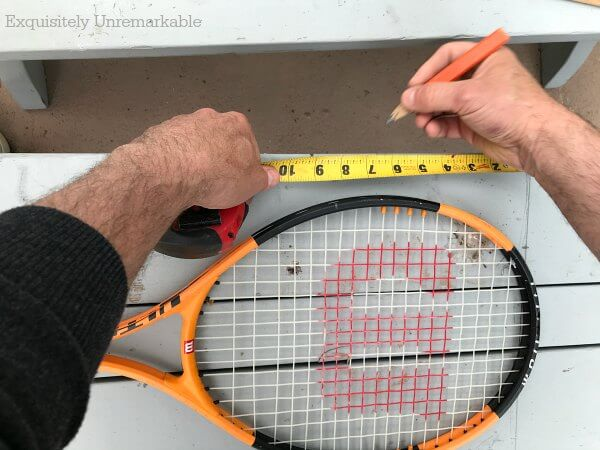 Measuring and marking a wooden bench with a pencil and a tennis racket