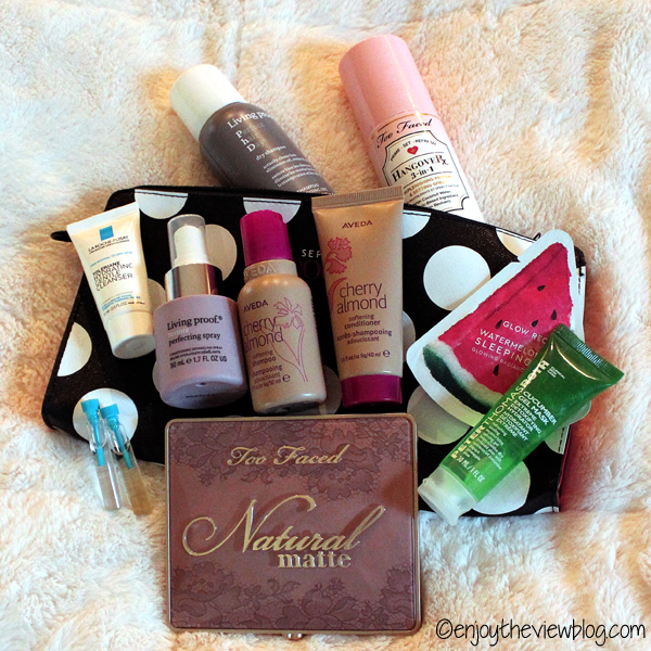 Multiple travel-sized beauty products lying on a fuzzy cream surface