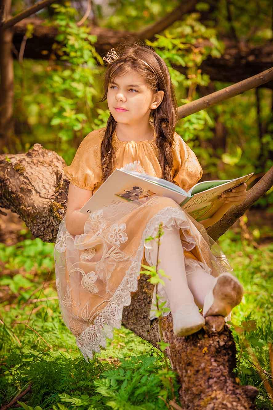 девочка сидя на ветке дерева читает книгу