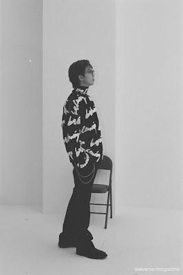 Czarno-białe zdjęcie RM'a stojącego bokiem, patrząc przed siebie