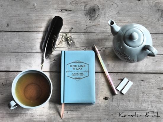 Stillleben mit Buch, Tee und Feder